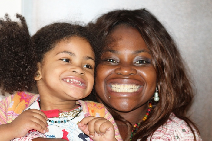 Carmelle with her daughter is smiling having zirconia crowns on her front teeth